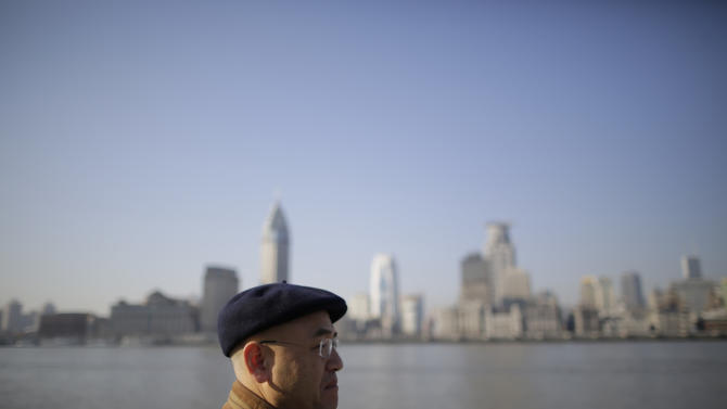 In this Jan. 28, 2013 photo, Chinese-born U.S. scientist Hu Zhicheng walks along the waterfront promenade of the Huangpu River in Shanghai, China. In Shanghai, he lives life as a free man, able to do anything except depart the country. Six thousand miles away in California, his family remains locked in their own emotional prisons: The wife who was left to raise two children alone. The son, just 13 when this started, who speaks bitterly of missing out on father-son moments. (AP Photo/Eugene Hoshiko)