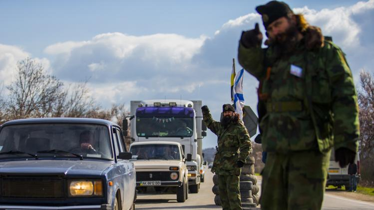 Members of Serbian Chetnik paramilitary groups Bratislav Zivkovic and Milutin Malisic direct traffic at a checkpoint on the highway between Simferopol and Sevastopol
