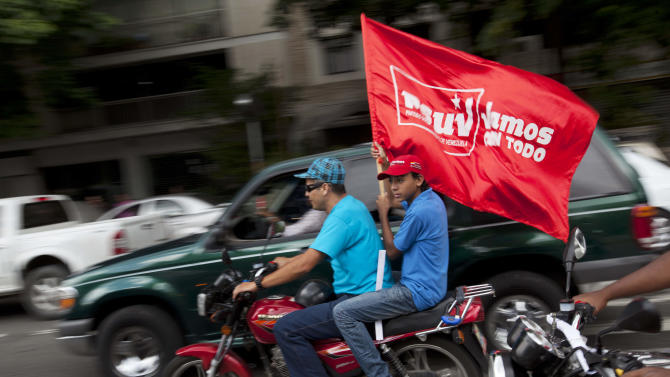 "A supporter of Venezuela's President Hugo Chavez holds a flag that reads in Spanish: ""We're going all out,"" while taking part in a campaign caravan through the streets of Caracas, Venezuela, Friday, Sept. 28, 2012. Venezuela's presidential election is scheduled for Oct. 7. (AP Photo/Rodrigo Abd)"