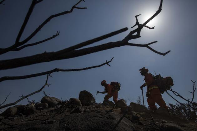 Hand crews work on the fire line after a wildfire near Point Mugu, Calif., Saturday, May 4, 2013. On Saturday, high winds and withering hot, dry air were replaced by the normal flow of damp air off th