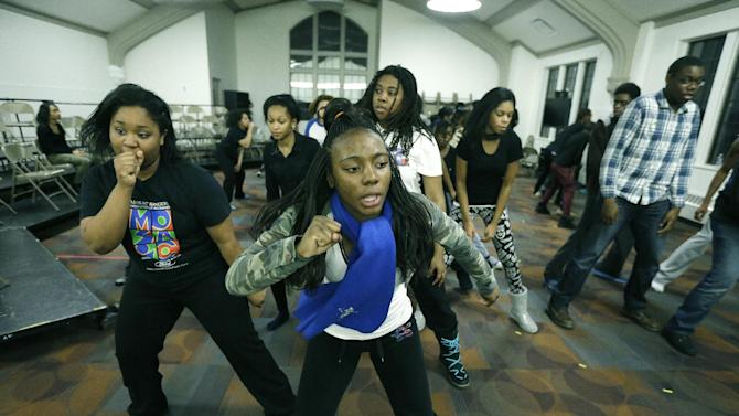 In this Feb. 26, 2014 photo, Jamiliah Minter performs with other members of the Mosaic Youth Theater in Detroit. Several privately-run youth organizations provide an array of extra-curricular options for high school kids. Roughly 165 young people engage in Mosaic's main programs each year - most from low- and moderate-income Detroit families. Minter aspires to a career either in entertainment or astronomy and is well aware of Detroit's problems, but is determined not to get sidetracked. (AP Photo/Carlos Osorio)
