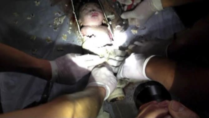 In this still image taken from video from Saturday May 25, 2013, rescue workers cut away the section of a sewage pipe where a newborn baby was trapped in Pujiang in east China's Zhejiang province. Chinese firefighters have rescued a newborn boy from a sewer pipe below a squat toilet, sawing out an L-shaped section and then delicately dismantling it to free the trapped baby, who greeted the rescuers with cries. A tenant heard the baby's sounds in the public restroom of a residential building in Zhejiang province in eastern China on Saturday and notified authorities, according to the state-run news site Zhejiang News. A video of the two-hour rescue that followed was broadcast widely on Chinese news programs and websites late Monday and Tuesday. (AP Photo) CHINA OUT