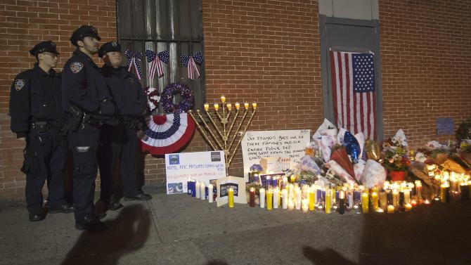 Police officers stand solemn at a makeshift memorial at the site where two police officers were shot in Brooklyn