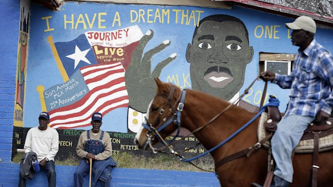 Riders pass a mural as they take part in a march honoring Martin Luther King Jr., Monday, Jan. 21, 2013, in San Antonio. The nation honors civil rights leader Martin Luther King Jr. on Monday, the same day as it celebrates the inauguration of the first black president to his second term. (AP Photo/Eric Gay)