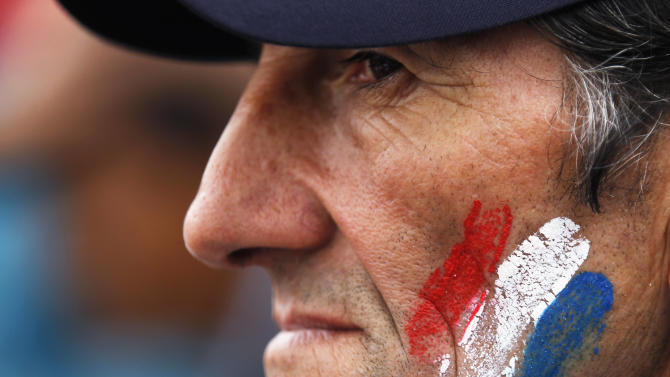 A supporter of Paraguay's President Fernando Lugo, whose face is painted with the colors of Paraguay's national flag, stands outside Parliament, in Plaza de Armas, where a large group gathered to protest against Lugo's impeachment trial, Asuncion, Paraguay, Friday, June 22, 2012. Paraguayan lawmakers voted Thursday to impeach Lugo for his role in a deadly clash involving landless farmers and police. Lugo's trial was to begin Friday in Paraguay's Senate. (AP Photo/Jorge Saenz)