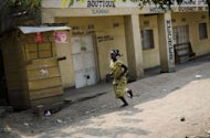 A woman runs away while rebels of the M23 group enter in the town of Rutshuru, that had already been deserted by the Congolese army, near the Ugandan border. Rebel fighters in the Democratic Republic of Congo seized control Sunday of more towns in the country's east, but said they would cede most of their gains to UN peacekeepers and police