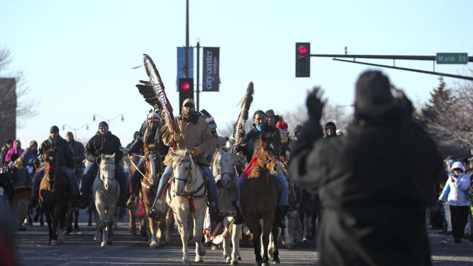 """The Dakota Wokiksuye Memorial Ride staff keeper Peter Lengkeek, of Crow Creek, S.D., center left, and Richard Milda, of Crow Agency, Mont, center right, led the riders into Reconciliation Park Wednesday, Dec. 26, 2012, in Mankato, Minn. The annual ride commemorates the 38 + 2 Dakota warriors hanged following the Dakota War of 1862. The """"Dakota 38"""" Memorial lists the names of all the Dakota warriors hanged in 1862. (AP Photo/The Star Tribune, David Joles)"""