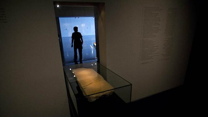 A museum worker walks next to the 'Gabriel Stone' as it is displayed at an exhibition at the Israel Museum in Jerusalem, Tuesday, April 30, 2013. An ancient stone with mysterious Hebrew writing and featuring the archangel Gabriel is being displayed in Israel, even as scholars continue to argue about what the inscription means.  (AP Photo/Sebastian Scheiner)