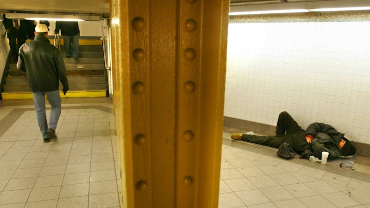 FILE- This file photo from Monday Feb. 27, 2006, shows a homeless man, right, lying inside a passageway at the Penn Station subway in New York.  (AP Photo/Bebeto Matthews, File)