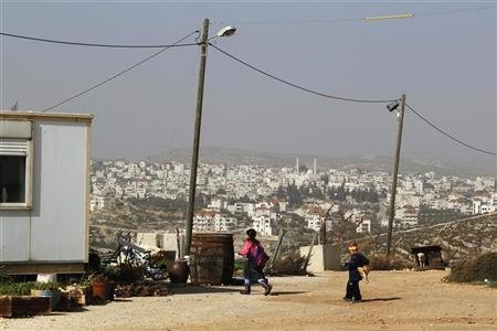 Jewish children walk near a temporary home in the unauthorized Jewish outpost of Migron near the West Bank city of Ramallah, as the Palestinian village of Deir Dibwan, where Israel's Supreme Court ruled the owners of Migron's land live, is seen in the background February 8, 2012. REUTERS/Baz Ratner