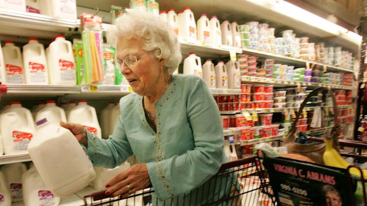FILE - In this Sept. 25, 2006 file photo, a shopper checks the expiration date on a gallon of milk while shopping during Senior Discount Day at Bi-Lo grocery, in Greenville, S.C. The rate of inflation for retirees tends to be higher than that for others,, especially in later years of retirement. A large chunk of their expenses often are from health care, and those costs are rising faster than overall inflation. (AP Photo/Mary Ann Chastain, file)