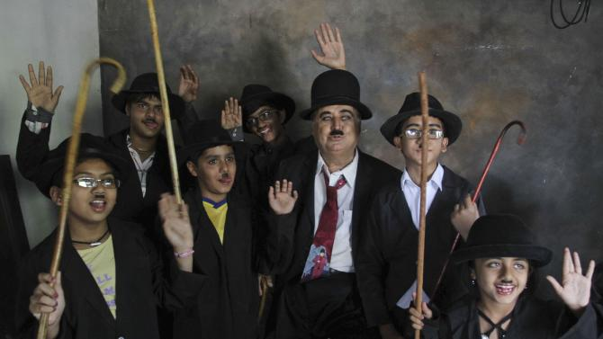 Members and supporters of the Charlie Circle, a Charlie Chaplin fan-club, gesture after getting ready for the annual parade to celebrate the birthday of Charlie Chaplin in Adipur, Gujarat state, India, Tuesday, April 16, 2013. Canes in hand and bowler hats firmly in place, dozens of Charlie Chaplin impersonators tramped through the streets of this small port town in western India on Tuesday to celebrate the birthday of the legendary comic actor and filmmaker. (AP Photo/Ajit Solanki)