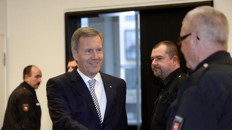 Former German President Wulff shakes hands with judicial employees as he enters the court room at the regional court in Hanover
