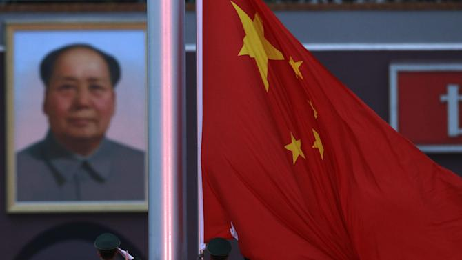 Chinese paramilitary policemen lower the Chinese national flag near a portrait of former Chinese leader Mao Zedong during a ceremony on Tiananmen Square in Beijing, China, Wednesday, Nov. 7, 2012. The Chinese Communist Party's 18th National Congress is scheduled to begin Nov. 8 in the Chinese capital. In addition to selecting members of the leading party bodies, the 2770 delegates hear and deliberate over the work of the party over the past five years, a party discipline report and revisions to the party constitution. (AP Photo/Ng Han Guan)
