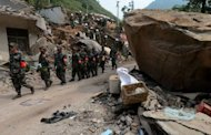 Chinese rescue workers search a house for survivors in Yunnan Province