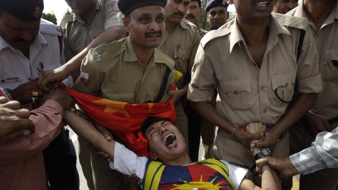 Indian policemen detain a lone Tibetan protestor who tried to stage a protest against the visit of Chinese Premier Li Keqiang outside the Chinese embassy, in New Delhi, India, Sunday, May 19, 2013. Just weeks after a tense border standoff, China's new premier headed to India on Sunday for his first foreign trip as the neighboring giants look to speed up efforts to settle a decades-old boundary dispute and boost economic ties.(AP Photo/Tsering Topgyal)