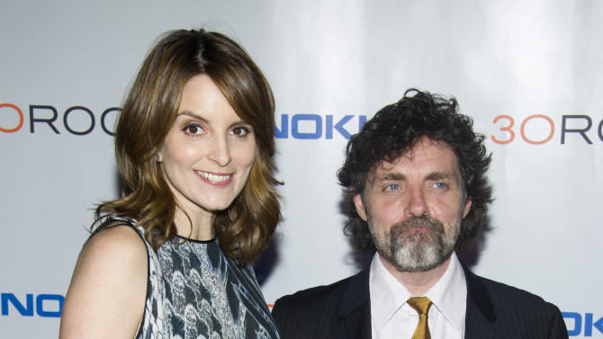 """FILE - This Dec. 20, 2012 file photo shows Tina Fey, left, and her husband Jeff Richmond at the """"30 Rock"""" farewell wrap party in New York. After seven seasons, """"30 Rock"""" airs its series conclusion Thursday at 8 p.m. EST on NBC. Fey serves as star, writer and creator of the series and Richmond is executive producer and the composer and arranger for the show.  (Photo by Charles Sykes/Invision/AP, file)"""