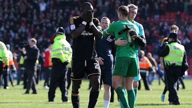 Abdoulaye Faye, left, burried his face in his hands following Hull's defeat at Barnsley