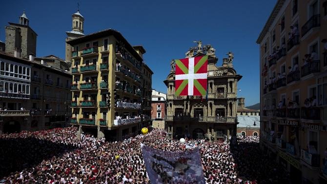 A Basque flag raised by pro independence supporters hangs in front of the town hall before the launch of the 'Chupinazo' rocket, to celebrate the official opening of the 2013 San Fermin fiestas, Saturday, July 6, 2013 in Pamplona, Spain in Pamplona July 6, 2013. The beginning of the festival was postponed for more than twenty minutes while authorities removed the flag. Revelers from around the world kick off the San Fermin festival with a messy party in the Pamplona town square, one day before the first of eight days of the running of the bulls glorified by Ernest Hemingway's 1926 novel 'The Sun Also Rises'. (AP Photo/Daniel Ochoa de Olza)