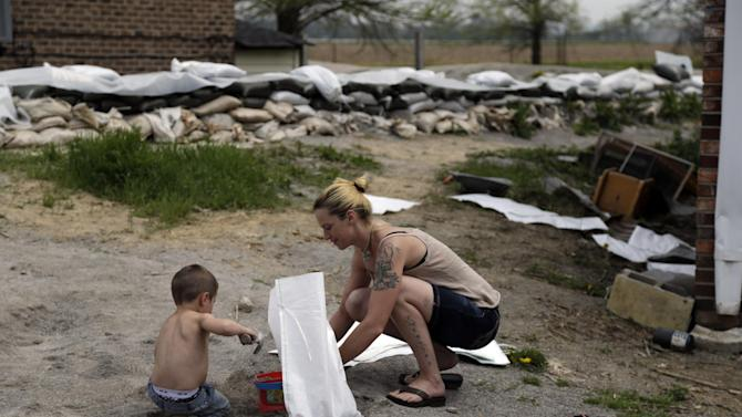 FILE - In this Tuesday, April 23, 2013 file photo, Dawn Moss, right, shows her 3-year-old son Sabastian Spangler how to fill a sandbag after the family finished building a temporary floodwall around their house in Dutchtown, Mo. The Mississippi River is expected to crest about 10 feet above flood stage Thursday at Dutchtown. The 100 or so residents in the southeast Missouri town have been seeking to have their homes bought out by the Federal Emergency Management Agency. But FEMA says Dutchtown has yet to supply an adequate cost-to-benefit analysis. (AP Photo/Jeff Roberson, File)