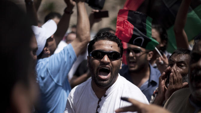 A Libya man chants revolutionary slogans while celebrating on election day in Martyrs' Square in Tripoli, Libya, Saturday, July 7, 2012. Jubilant Libyan voters marked a major step toward democracy after decades of erratic one-man rule, casting their ballots Saturday in the first parliamentary election after last year's overthrow and killing of longtime leader Moammar Gadhafi. But the joy was tempered by boycott calls, the burning of ballots and other violence in the country's restive east. (AP Photo/Manu Brabo)