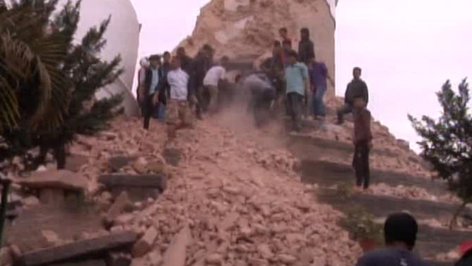 In this image from AP video people search in a buildings rubble in Kathmandu, Nepal after a strong earthquake hit the area Saturday April 25, 2015. A strong magnitude-7.9 earthquake shook Nepal's capital and the densely populated Kathmandu Valley before noon Saturday, causing extensive damage with toppled walls and collapsed buildings, officials said. (AP video via AP)