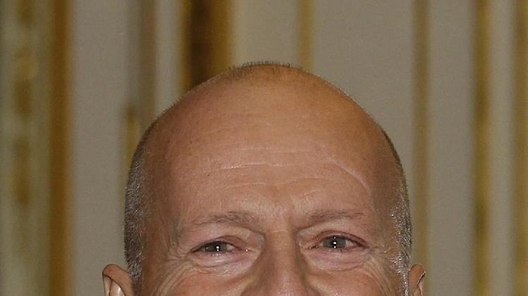 American movie star Bruce Willis smiles after being awarded with the medal of Commander of Arts and Letters by French culture minister Aurelie Filippetti, in Paris, Monday Feb. 11, 2013.(AP Photo/Remy de la Mauviniere)