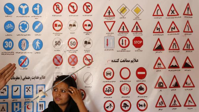 A woman listens to an instructor who explains traffic signs at a driving school in Kabul