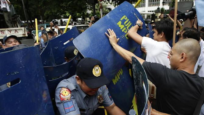 Protesters clash with police officers as they try to get closer to the U.S. Embassy in a protest to mark Philippine-American Friendship Day Friday, July 4, 2014 in Manila, Philippines. The protesters have clashed with police near the U.S. Embassy in Manila, where about 100 of them marched to mark Philippine-American Friendship day with a call to junk a new pact allowing thousands of U.S. troops to be temporarily based in the country. (AP Photo/Bullit Marquez)