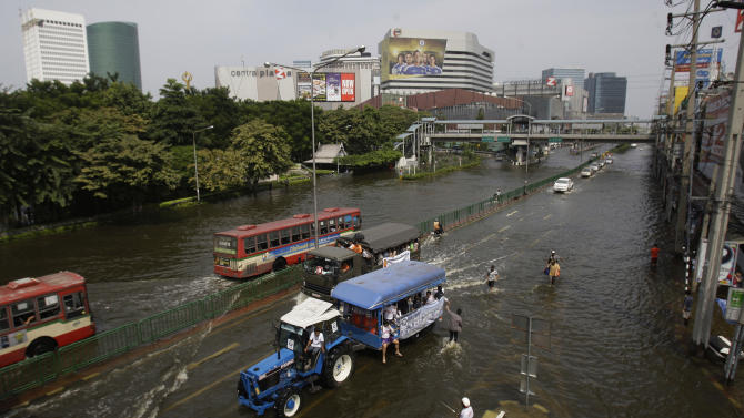 A traktor ferries stranded people along flooded streets at the Lad Phrao district in Bangkok, Thailand, Saturday, Nov. 5, 2011. Thailand's record floods continued to creep towards inner Bangkok. (AP Photo/Aaron Favila)