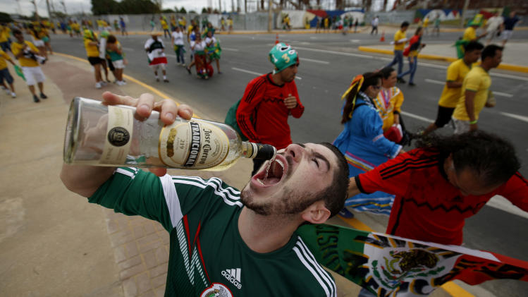 A Mexican fans drinks tequila outside of the Arena Castelao stadium before the group A World Cup soccer match between Brazil and Mexico in Fortaleza, Brazil, Tuesday, June 17, 2014. Many of the soccer fans traveling from the U.S. to Brazil, are part of the last great wave of Mexican migration to the United States, which spanned the 1990s to the mid-2000s. Others are second-generation Mexicans who grew up rooting for the Mexican team at a time when Team USA was still unknown. (AP Photo/Eduardo Verdugo)