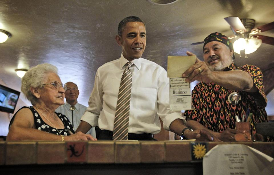 President Barack Obama is shown an old photograph by Robert Romero, owner of Romero's Cafe and Catering, right, Thursday, Aug. 9, 2012, in Pueblo, Colo. Also at the counter with Obama Virginia Romero, left, who founded the establishment. (AP Photo/Pablo Martinez Monsivais)