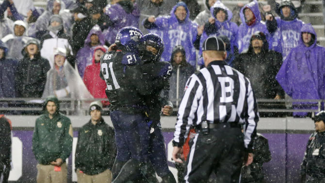 TCU running back Kyle Hicks (21) and quarterback Trevone Boykin, right, celebrate a touchdown scored by Boyking on a running play in the first overtime of an NCAA college football game against Baylor, Friday, Nov. 27, 2015, in Fort Worth, Texas. TCU won in twos overtimes, 28-21. (AP Photo/Tony Gutierrez)