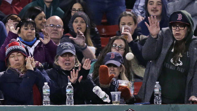 Fans grimace as a foul ball, off the bat of Boston Red Sox Xander Bogaerts, knocks over a water bottle in front of them during the seventh inning of a baseball game against the Atlanta Braves at Fenway Park in Boston, Thursday, April 28, 2016. (AP Photo/Charles Krupa)