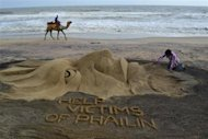 Indian sand artist Sudarshan Pattnaik works on a sand sculpture about Cyclone Phailin that hit Puri in the eastern Indian state of Odisha October 14, 2013. REUTERS/Stringer