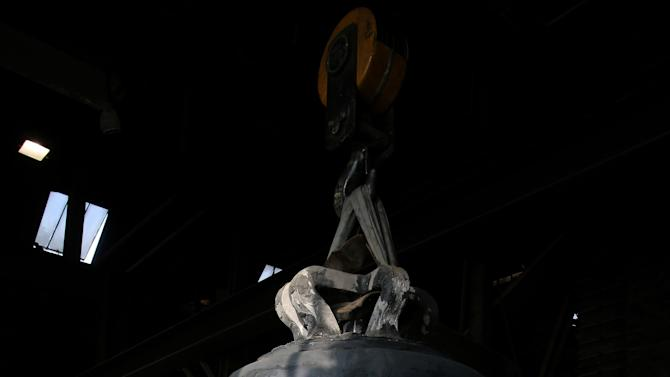 "A founder looks at the new bell bound for Notre Dame cathedral in Paris, ""Gabriel"" is seen Friday, Dec. 7, 2012, in the foundry of Villedieu les Poeles, Normandy, France.  Paris' Notre Dame Cathedral will be celebrating its 850th anniversary starting Wednesday Dec. 12, 2012,  and Gabriel will join the peal of bells at the medieval landmark cathedral. (AP Photo/David Vincent)"