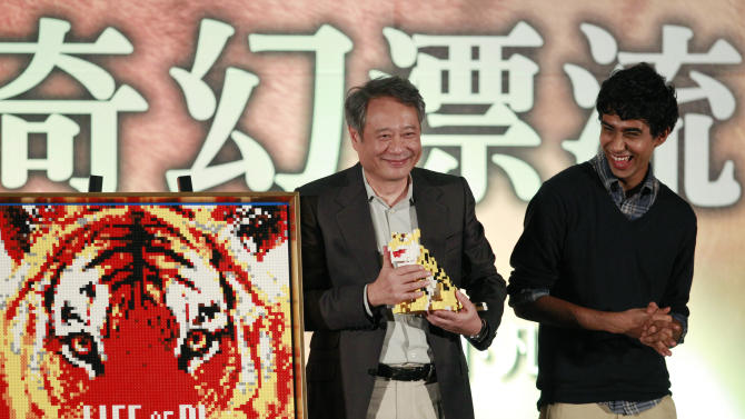 "Taiwanese director Ang Lee, left, and lead actor from India Suraj Sharma accept gifts a during press conference announcing their new film ""Life of Pi,"" in Taipei, Taiwan, Wednesday, Nov. 7, 2012. ""Life of Pi"" is an upcoming 3D adventure film based on the 2001 novel of the same name by Yann Martel, staring Sharma and directed by Lee. (AP Photo/Wally Santana)"