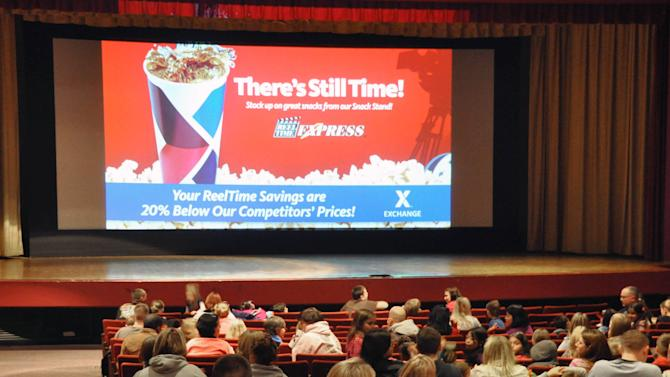 "Movie patrons wait for the showing of ""Hotel Transylvania"" inside the theater on Ellsworth Air Force Base in South Dakota on its last day of operation, Saturday, Jan. 19, 2013. The Army and Air Force Exchange Service theater serving airmen and their families is one of 60 across the globe that's closing because it's too expensive to switch from 35 millimeter film prints to an all-digital projection format. (AP Photo/Dirk Lammers)"