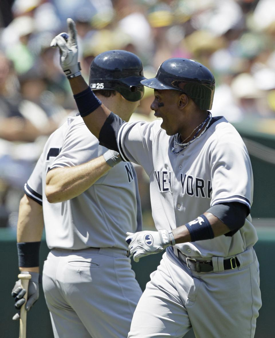 New York Yankees' Curtis Granderson, right, is greeted by teammate Mark Teixeira, left, after hitting a home run against the Oakland Athletics during the fourth inning of their baseball game Sunday, July 22, 2012 in Oakland, Calif.  (AP Photo/Eric Risberg)