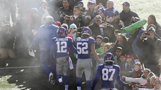 New York Giants wide receiver Jerrel Jernigan (12), Spencer Paysinger (52) and Domenik Hixon (87) greet a contingent of teachers, parents, and students from Sandy Hook Elementary School in Newtown, Conn., before an NFL football game Sunday, Dec. 30, 2012, in East Rutherford, N.J. The school was the site of a mass shooting on Dec. 14. (AP Photo/Peter Morgan)