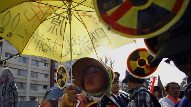 A protester holds an umbrella with slogans written on during an anti-nuclear demonstration in Tokyo, Saturday, March 9, 2013. Gathering on a weekend ahead of the second anniversary of the March 11 quake and tsunami that sent Fukushima Dai-ichi plant into multiple meltdowns, demonstrators said they would never forget the world's worst nuclear catastrophe, and expressed alarm over the government's eagerness to restart reactors. (AP Photo/Junji Kurokawa)