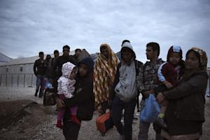 Refugees and migrants walk to cross the border from…