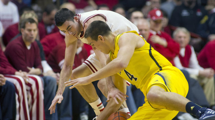 Michigan's Mitch McGary (4) and Indiana's Will Sheehey (0) battle for a loose ball during the first half of an NCAA college basketball game Saturday, Feb. 2, 2013, in Bloomington, Ind. (AP Photo/Doug McSchooler)