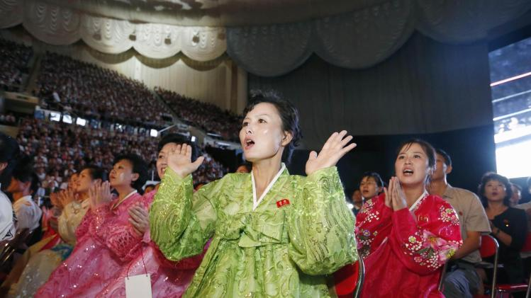 North Korean women wearing traditional costume react as they watch professional wrestling exhibition matches in Pyongyang