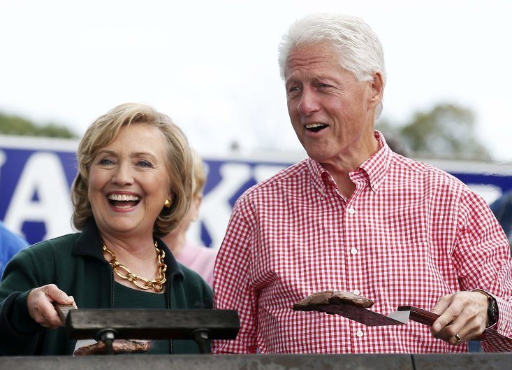 Former U.S. Secretary of State Hillary Clinton and her husband, former U.S. President Bill Clinton, hold up some steaks at the 37th Harkin Steak Fry in Indianola, Iowa, on Sept. 14, 2014. (REUTERS/Jim Young)