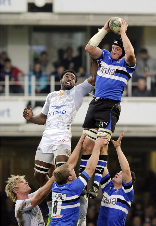 CORRECTS IDENTITY Bath's Stuart Hooper, top right, wins the lineout ball from Montpellier's Fulgence Ouedraogo during their Heineken Cup pool 3 rugby match at the Recreation ground, Bath, England, Sun