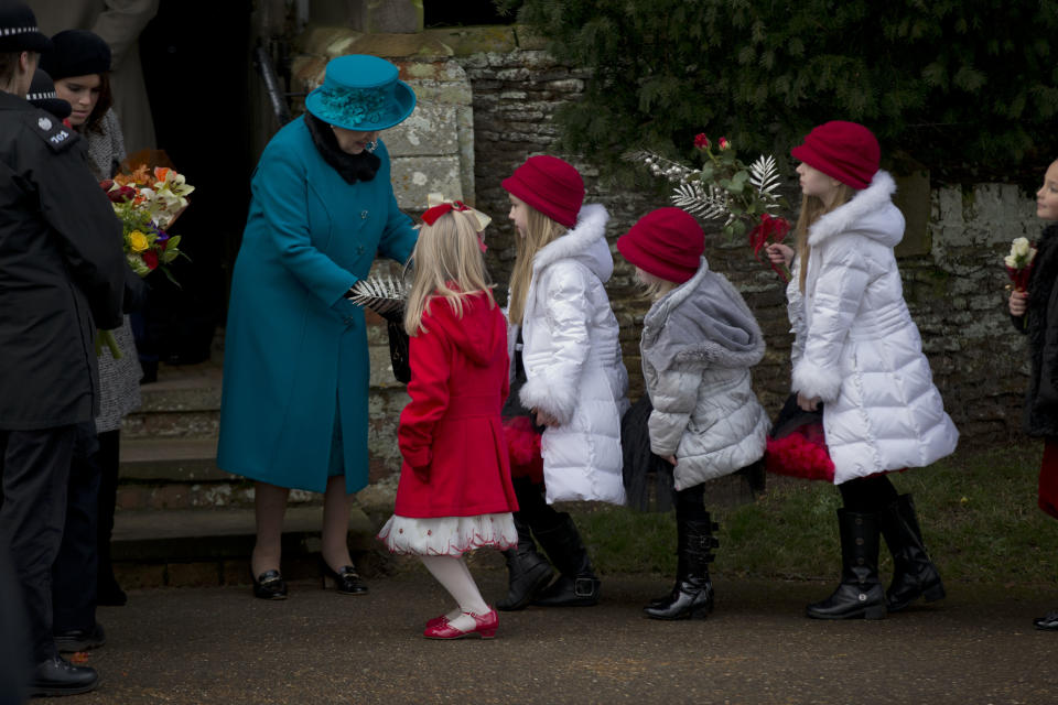 Britain's Queen Elizabeth II receives flowers from children after attending the British royal family's traditional Christmas Day church service in Sandringham, England, Tuesday, Dec. 25, 2012.  (AP Photo/Matt Dunham)