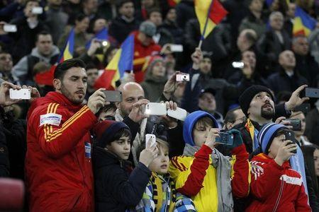 Fans take pictures with their phones at the beginning of the international friendly soccer match between Romania and Argentina at the National Arena in Bucharest