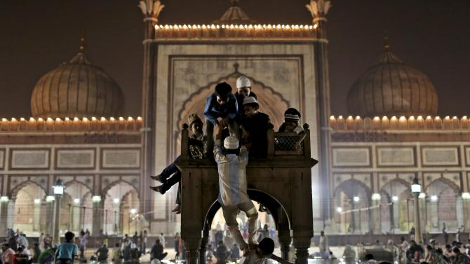 Indian Muslim boys play atop a marble stand after breaking their fast on the last day of the holy month of Ramadan before the Eid holiday, at Jama Masjid in New Delhi, India, Sunday, Aug. 19, 2012. Muslims around the world celebrate Eid al-Fitr, marking the end of Ramadan, the Muslim calendar's ninth and holiest month during which followers are required to abstain from food and drink from dawn to dusk. (AP Photo/Kevin Frayer)