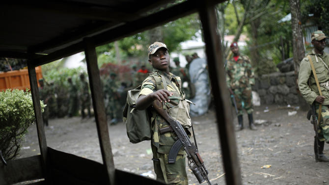 M23 rebels withdraw from the eastern Congo town of Goma, Saturday Dec. 1, 2012. Sy Koumbo, a spokesman for the U.N. in Congo, says that an agreement was reached late Friday with M23 rebels after they attempted to force their way into Goma's international airport to seize arms. Koumbo says U.N. peacekeepers blocked the fighters. Trucks full of M23 rebels drove Saturday along the road that leads out of Goma towards Kibumba, where the rebels are supposed to settle following an agreement reached in Kampala last week. M23 soldiers were cheering as they did a final tour in the city center. (AP Photo/Jerome Delay)
